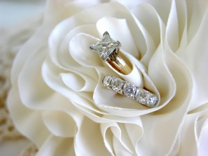 A set of diamond wedding rings in the folds of the bride's dress.