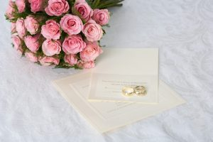 Wedding bouquet of pink roses and wedding rings on invitation